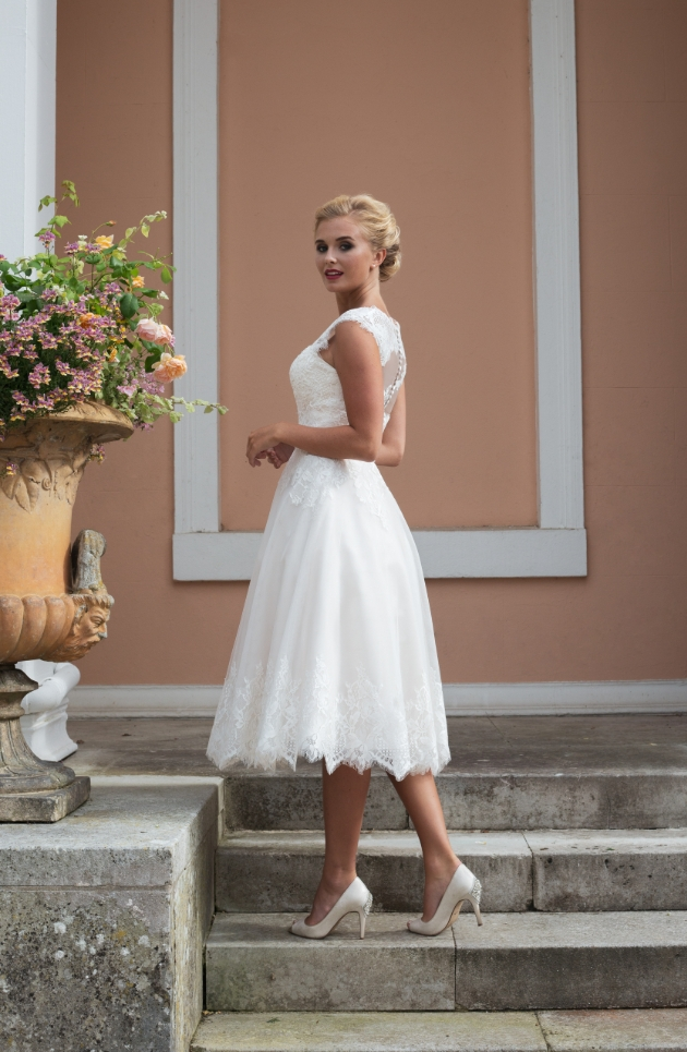 A short ivory lace and tulle gown model is on the steps of a villa