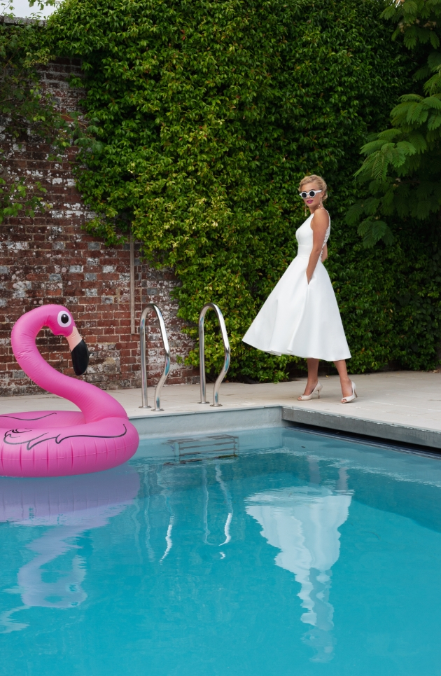 A full-skirted Mikado dress featuring a halter style neckline model is standing by the pool