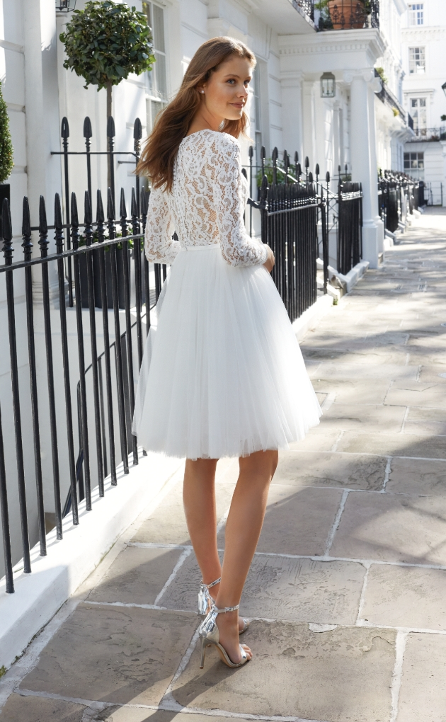 Model is on a street path wearing ivory dress featuring a knee-length tulle skirt and illusion beaded lace bodice