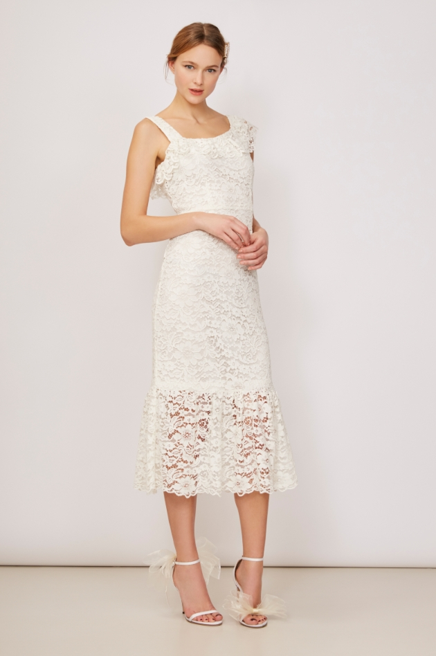 Model is in a studio and wearing an ivory floral lace dress