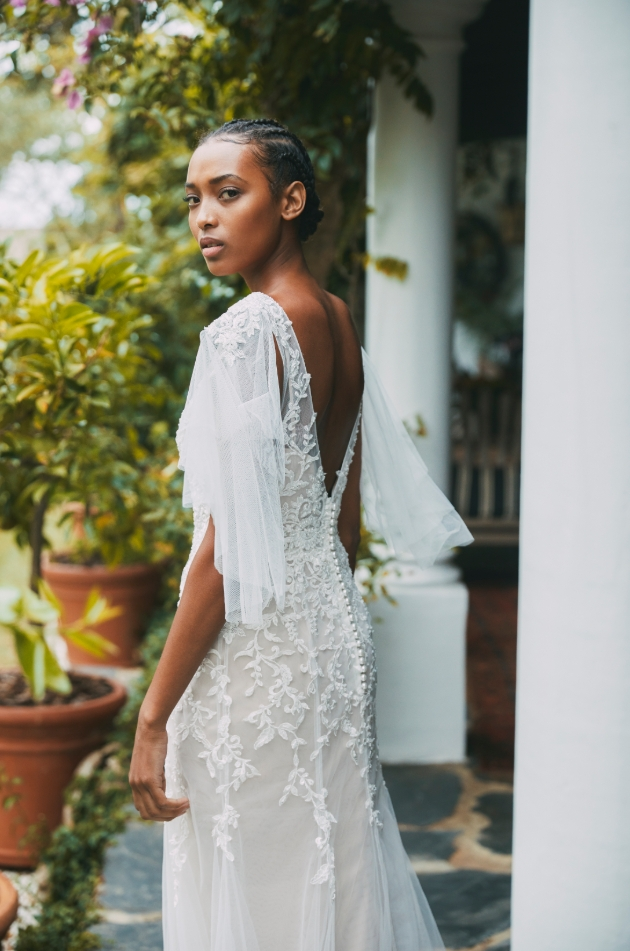 Model wears gown with v-back neckline and billowing sleeves