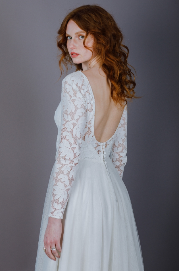 Model wears large lace patterned bodice with sleeves and tulle skirt