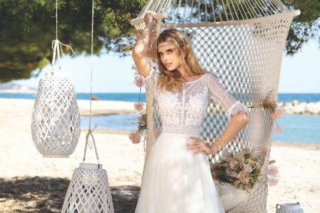 Ladybird collection dress with model in sleeved gown on the beach in front of a macrame backdrop