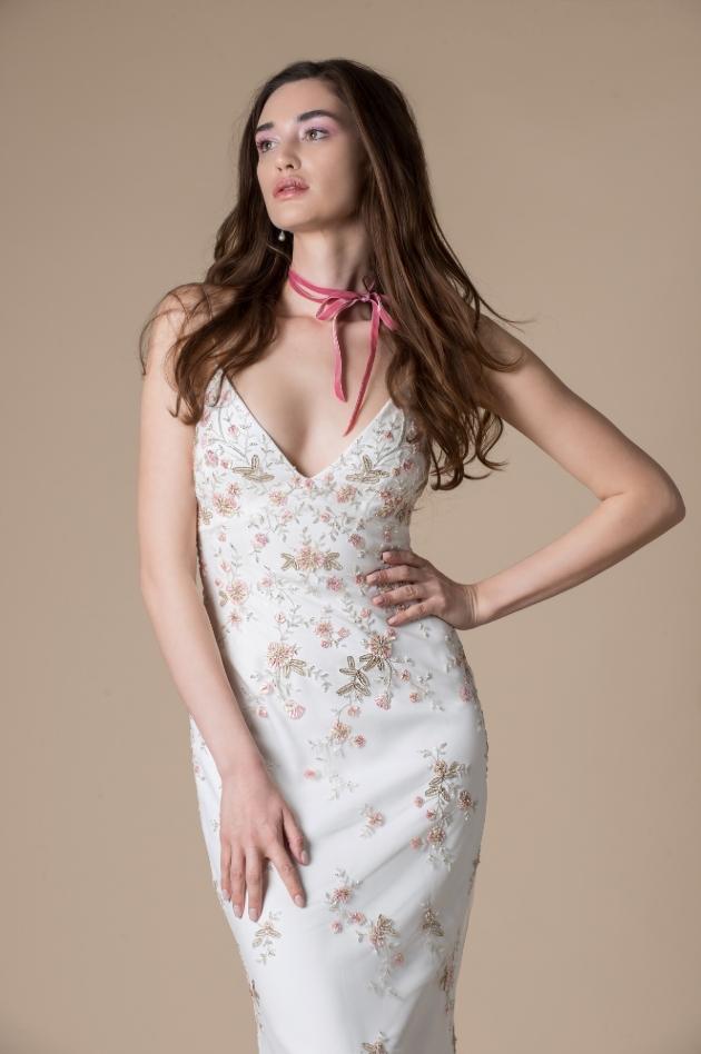 Model wears slimline dress with coloured flower detail
