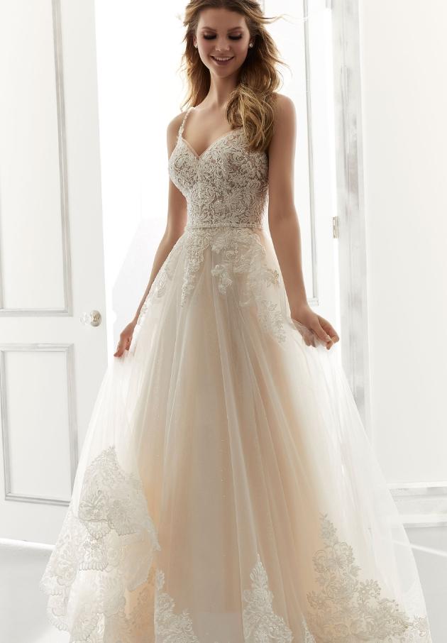 Model wears Annabel gown standing in front of window