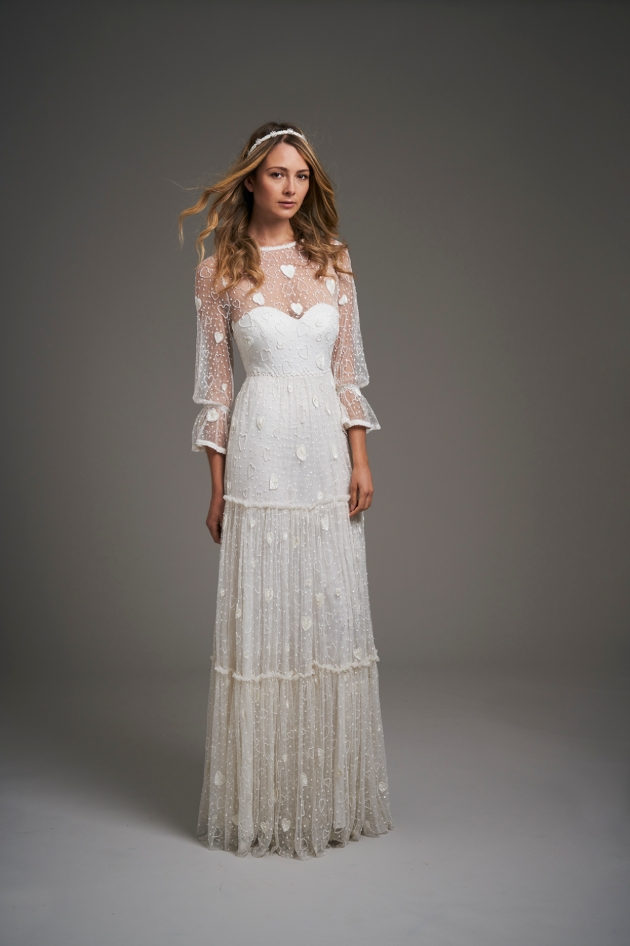 Model in a studio wearing a tiered pretty detailed wedding gown