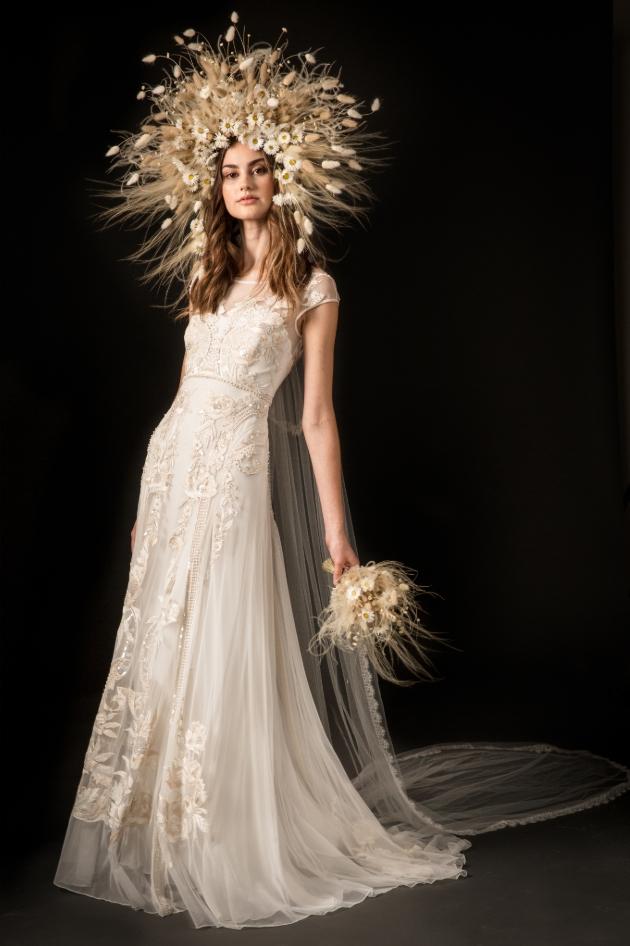 Model in a studio setting wears wedding dress with large headdress