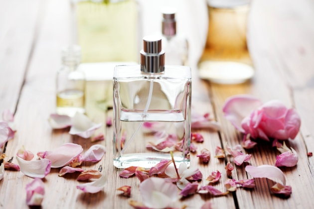 Perfume bottle on a table surrounded by flowers