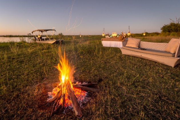 sofa on the grass next to a table and a lit campfire early evening