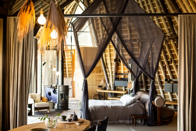 inside a safari-style lodge bedrooms set up with canopy over the bed