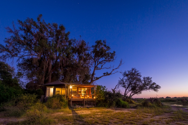 safari lodge at night lit by camp lights looking out on to bush