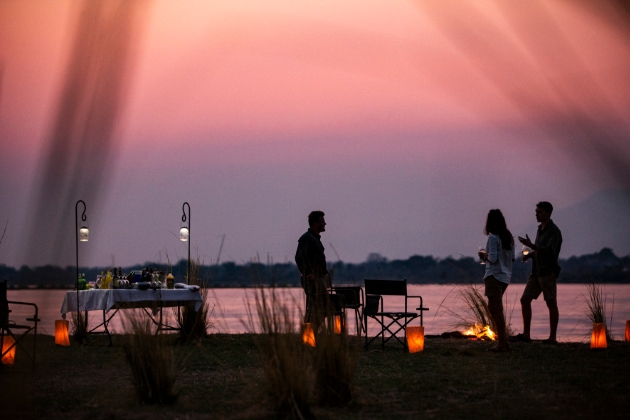 couple having dinner with a friend outside at night by waterhole