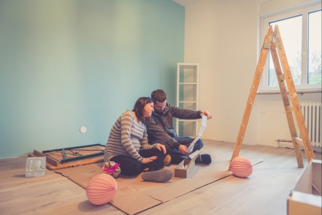 couple in room which is being decorated and the woman is pregnant