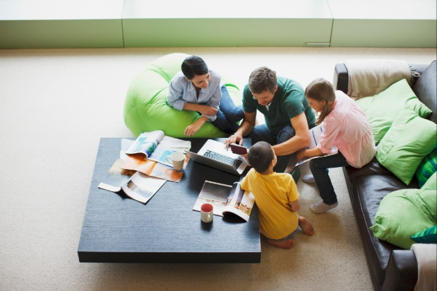 Two adults and two children on floor in lounge area looking at a laptop