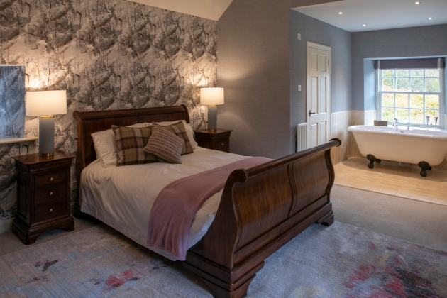 image of a wooden bed in a newly refurbished bedroom with bathtub