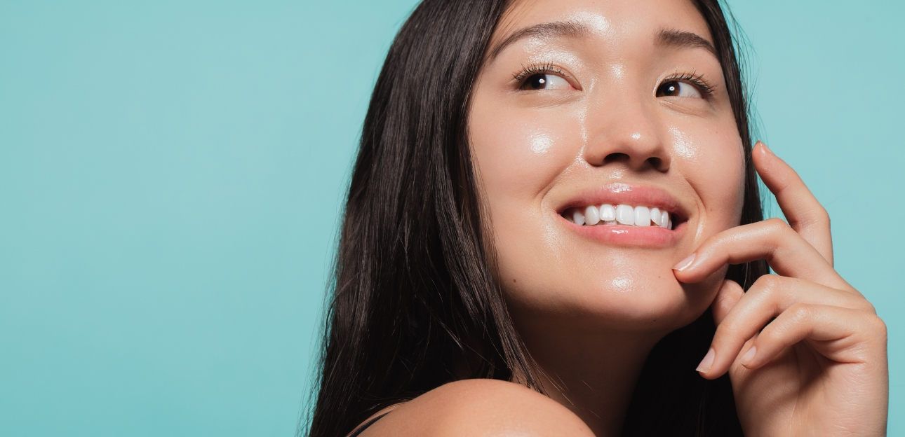 Young woman with glowing skin against a blue background