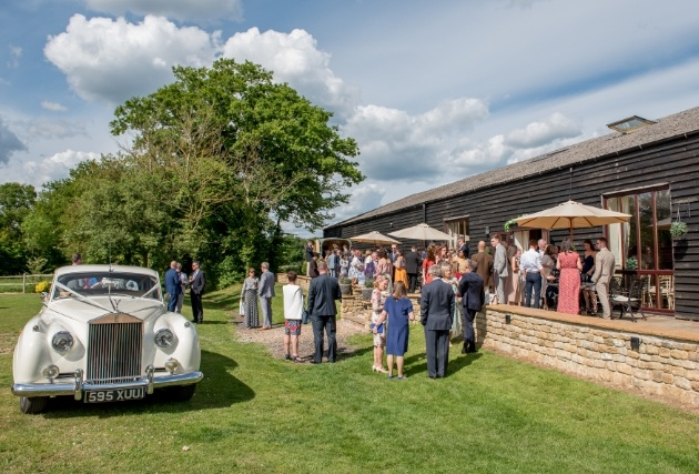 outdoors terrace adjacent to barn, people milling about wedding car on grass sunny day