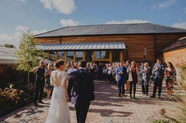 front of barn with bride and groom and guests