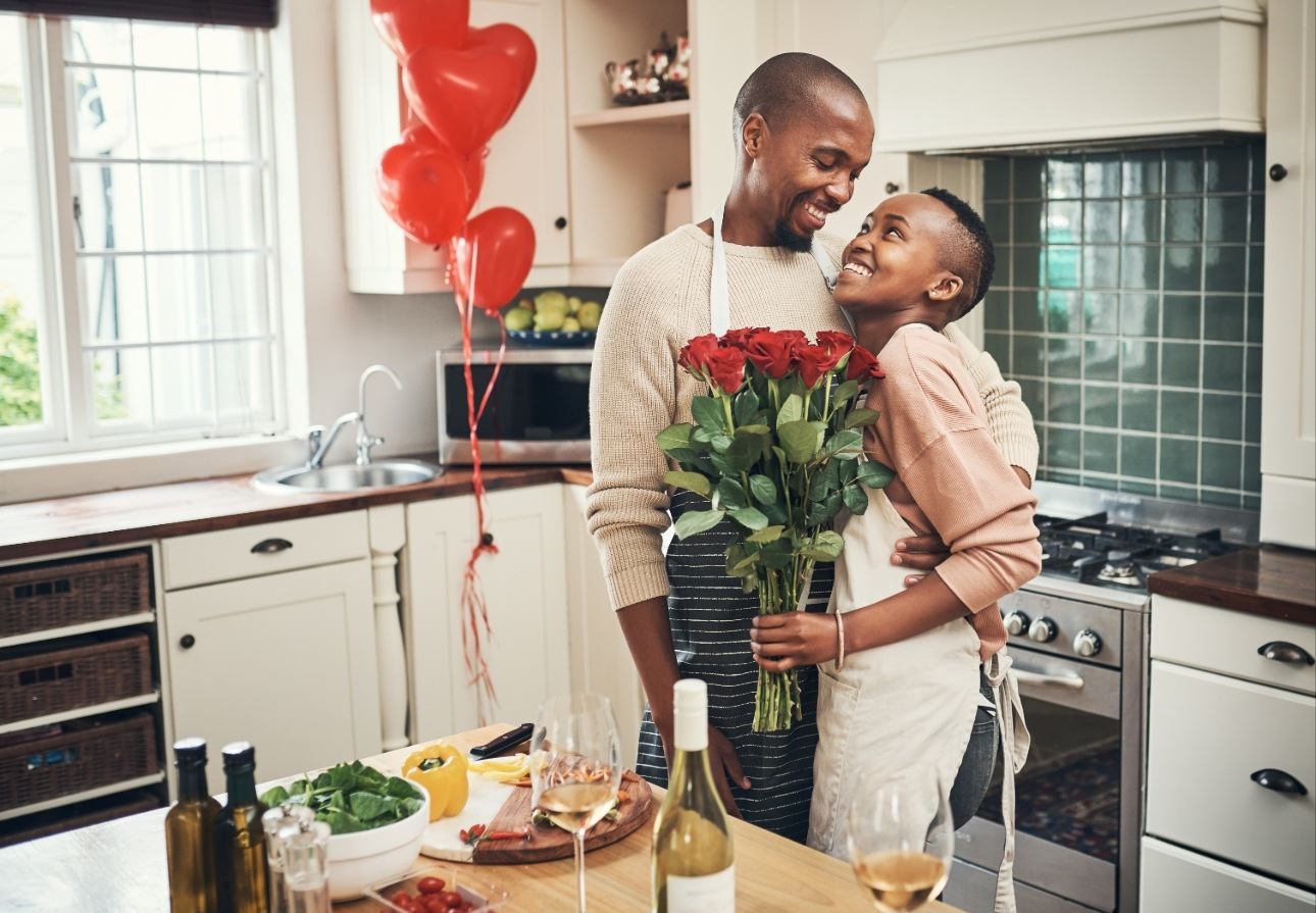couple in kitchen cooking being romantic