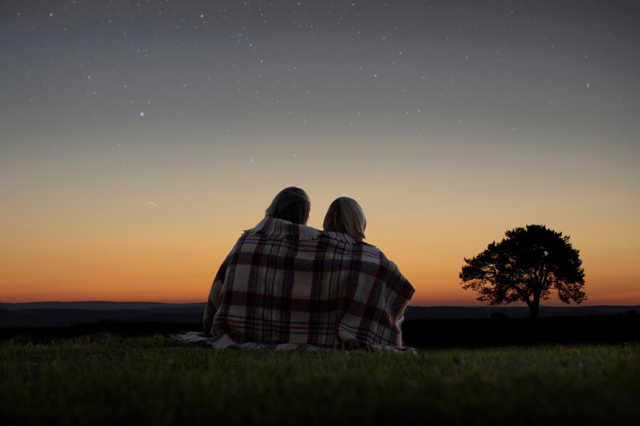 couple in a blanket at night looking at the night sky