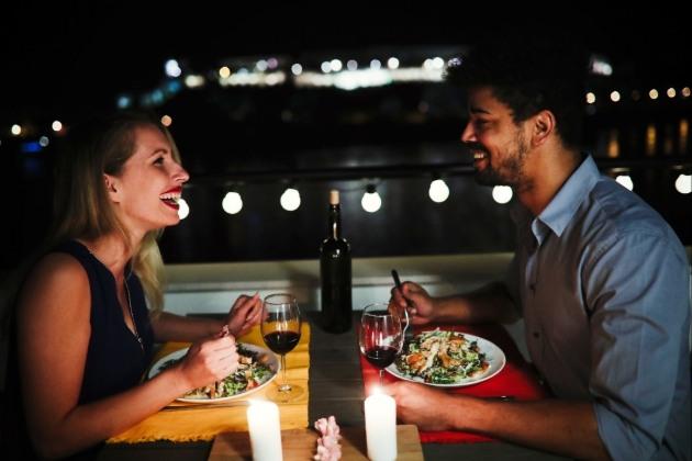 couple having dinner on a balcony at night