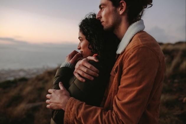 couple in coats on a hillside looking out at the view the same way he is hugging her