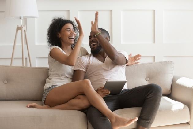 couple on sofa with ipad high-fiving