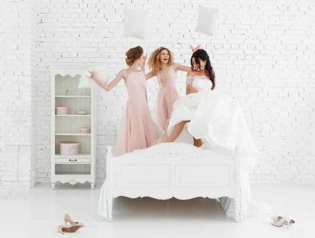 bride and bridesmaids on bed jumping happy