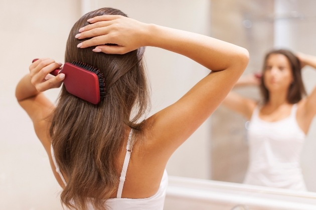 Woman with healthy hair bushing her hair in the mirror