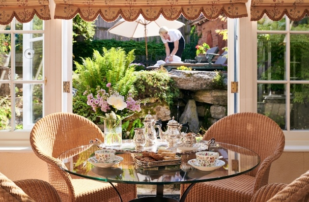 afternoon tea set at table doors open to gardens
