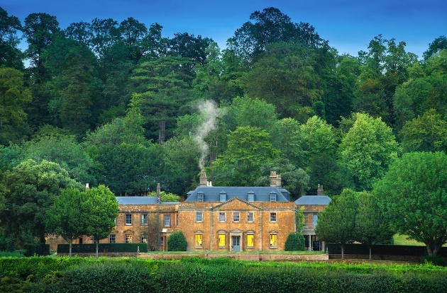 grand house surrounded by woodland