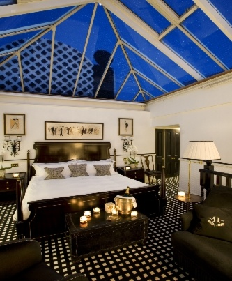 black and white styled room at night with candles in the room and glass roof