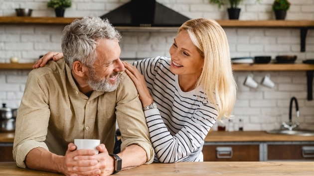 older couple leaning on kitchen table embracing