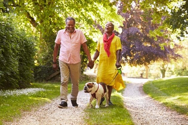 older couple walking dog in park