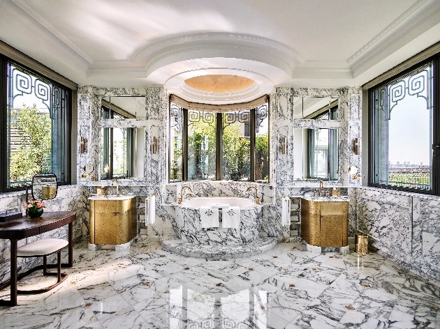 marble and gold bathroom centre round bath windows either side