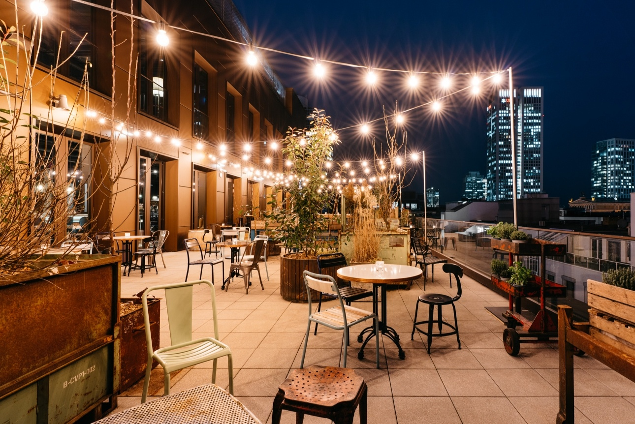 hotel roof terrace with bar and fairy-lights and chairs at night