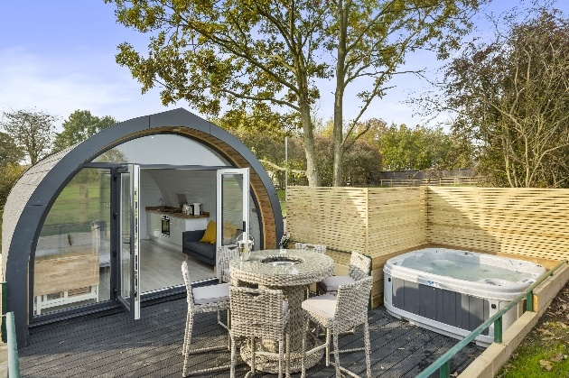 pod with fenced off space hot tub and tables and chairs outside