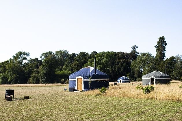 yurt in field with fire pit with other yurts in background