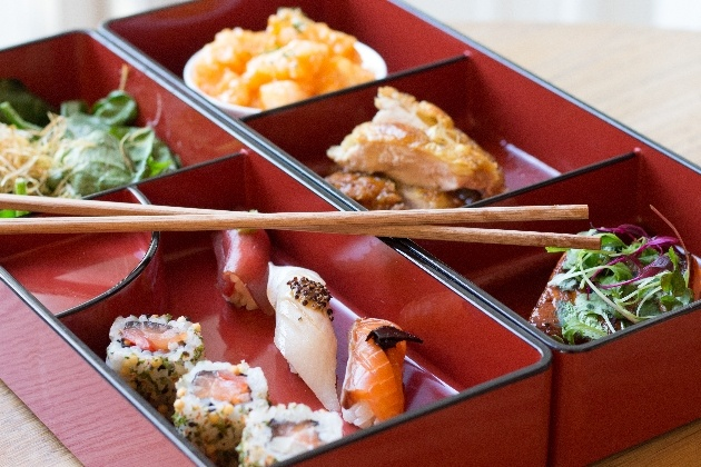 closeup of sushi presented in nice bowl with chopsticks