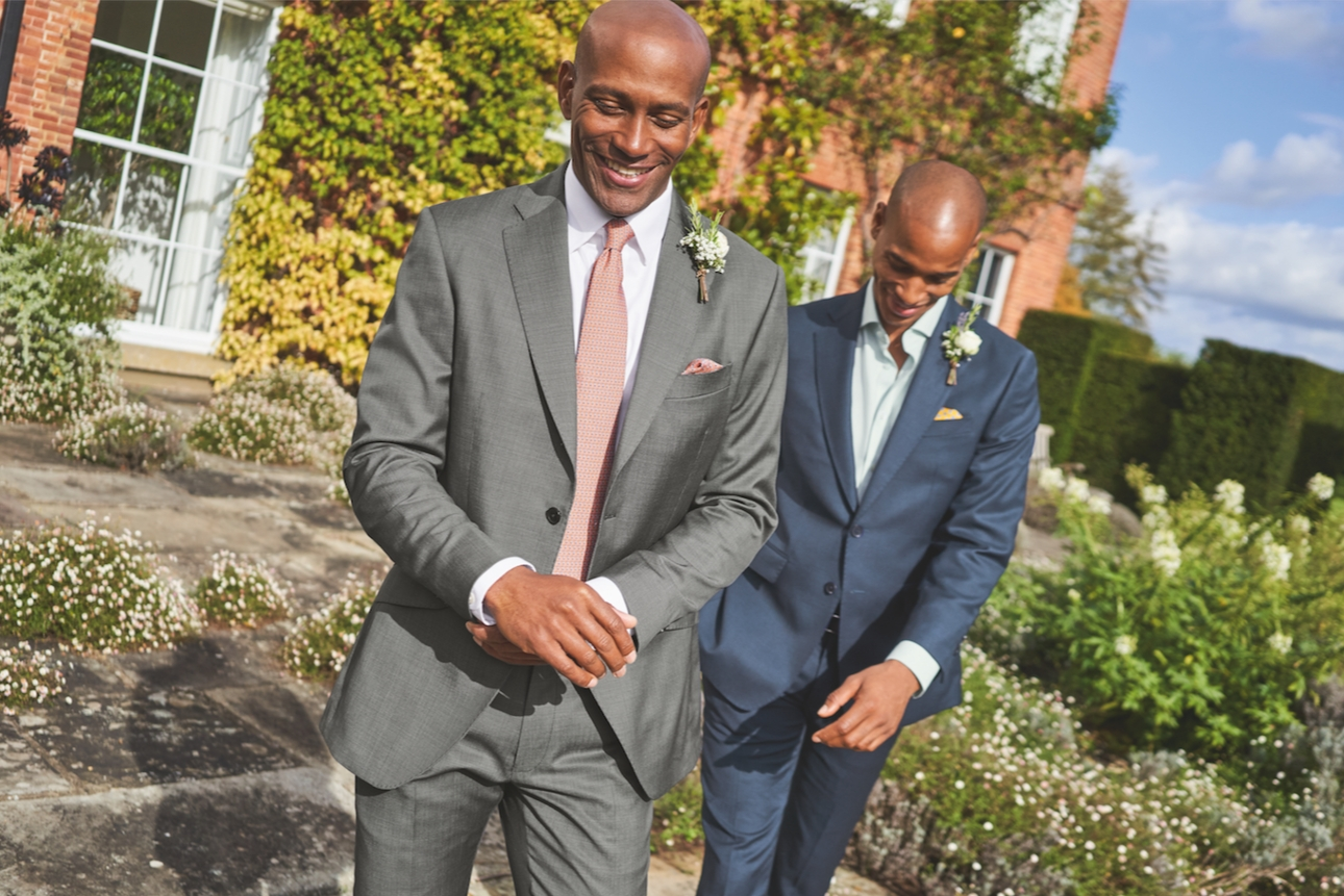 two men in suits one grey and one blue suit