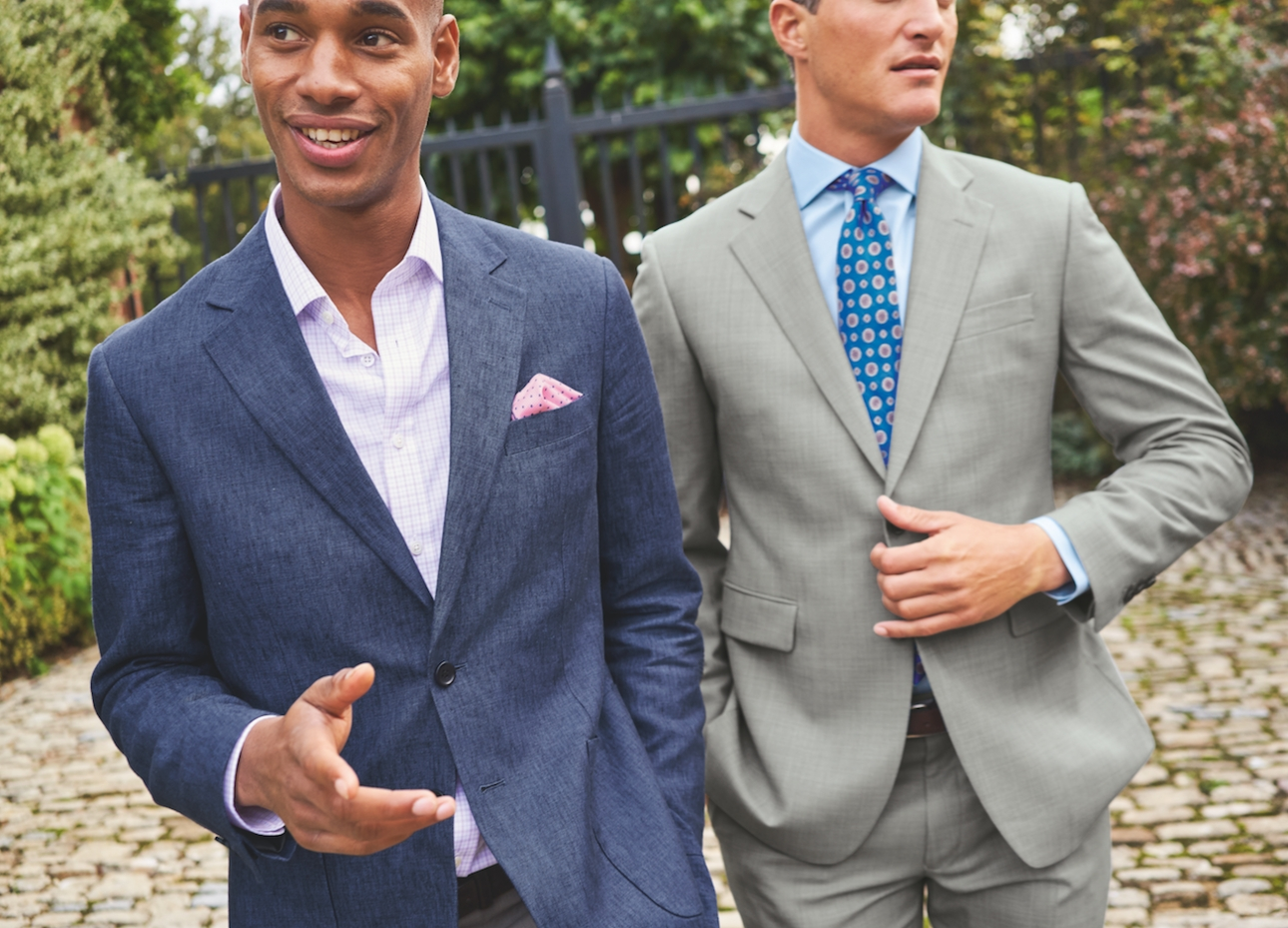 two male models in suites one grey with tie and one blue no tie