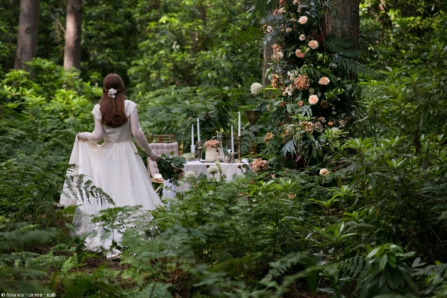 bride in woods walking to table set up