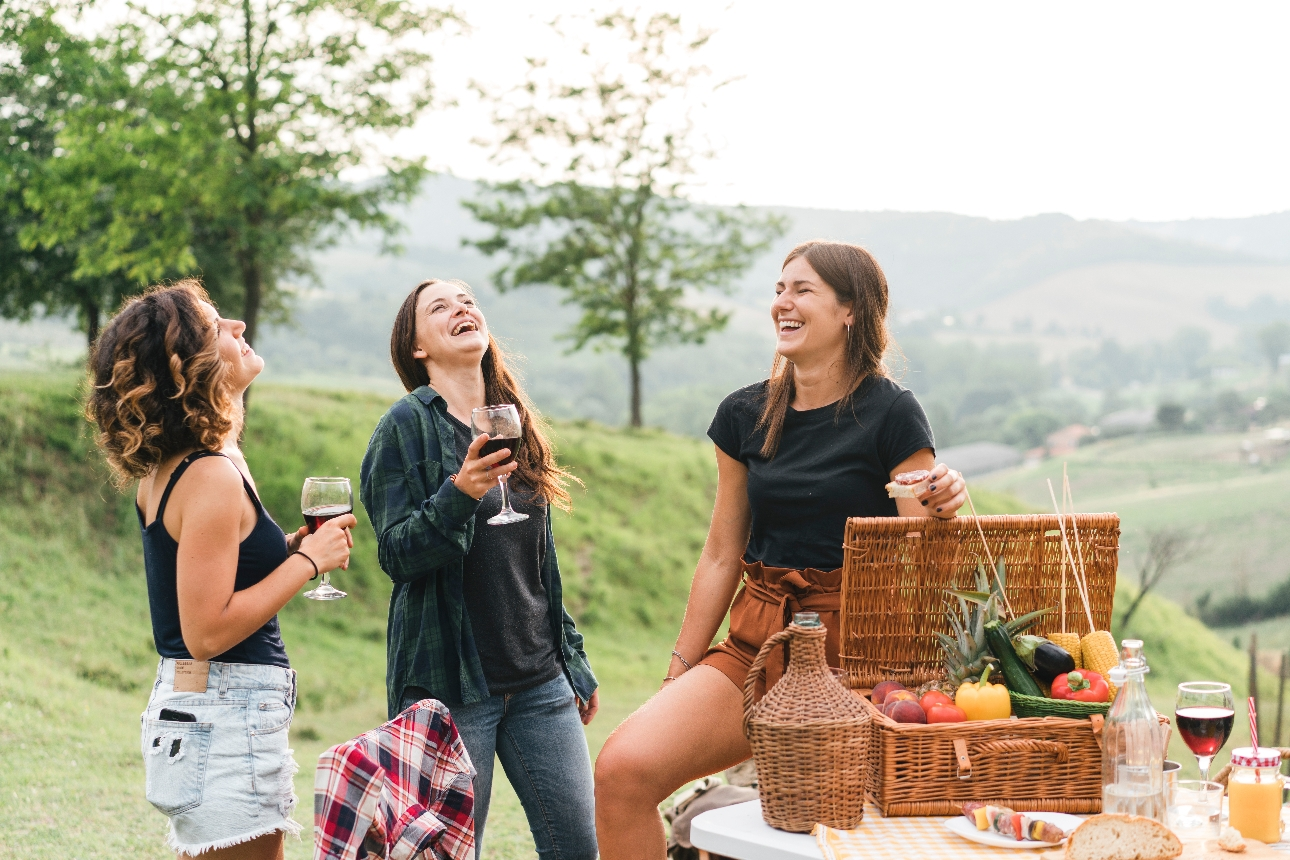 three friends outside with picnic