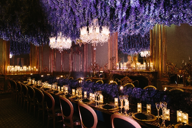 dark room candle lit purple flowers hanging from ceiling