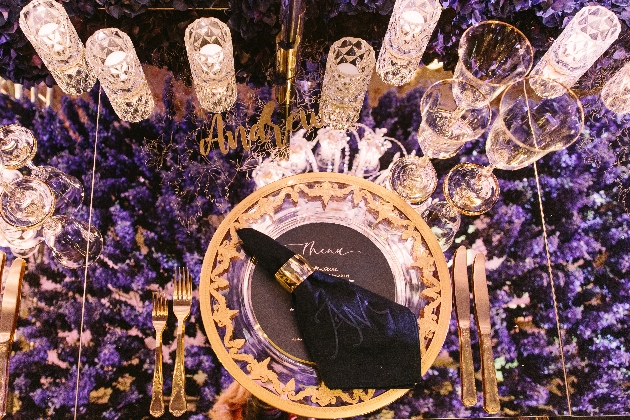 table setting with crystal glassware and purple blooms