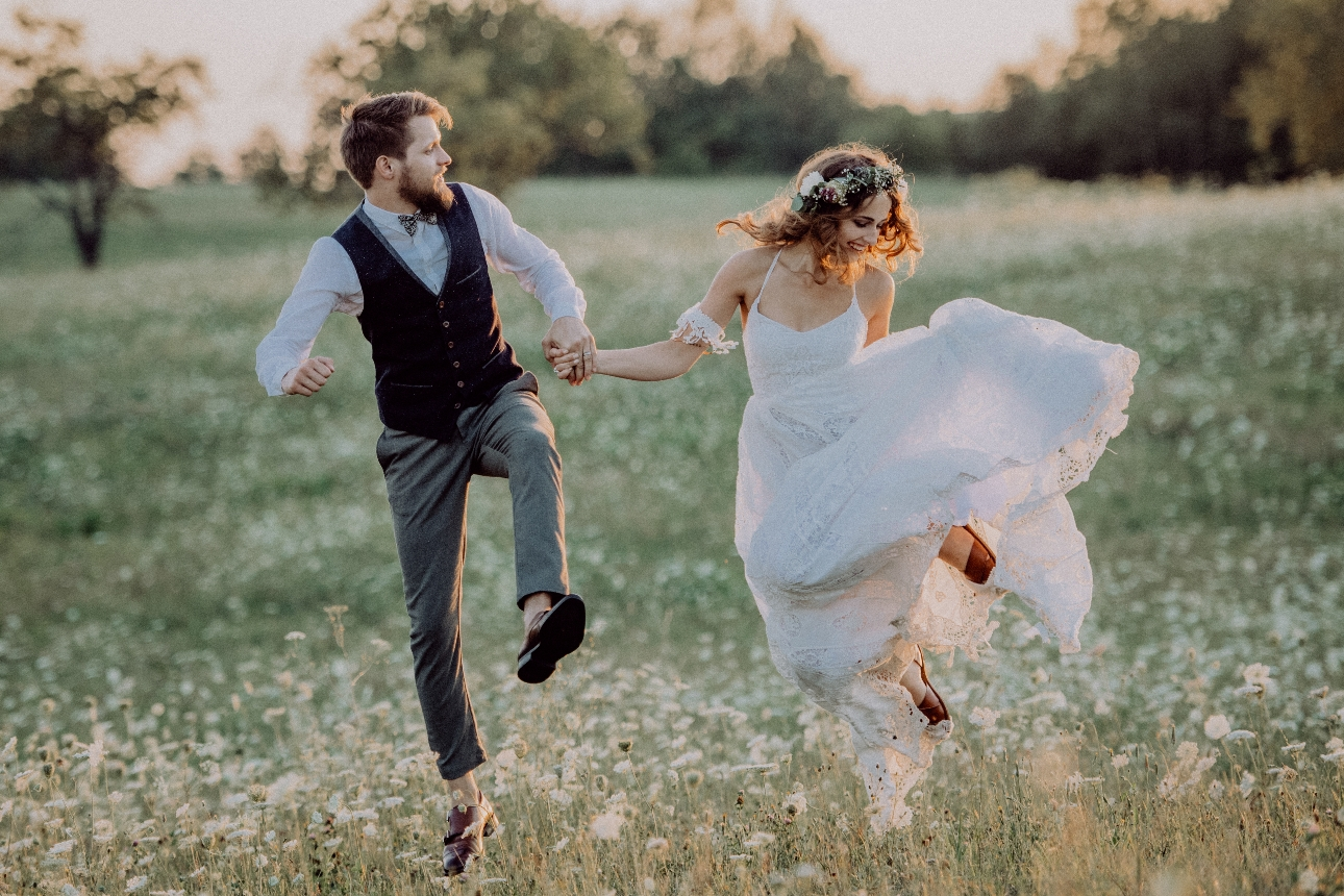 couple in wedding gear jumping in the air