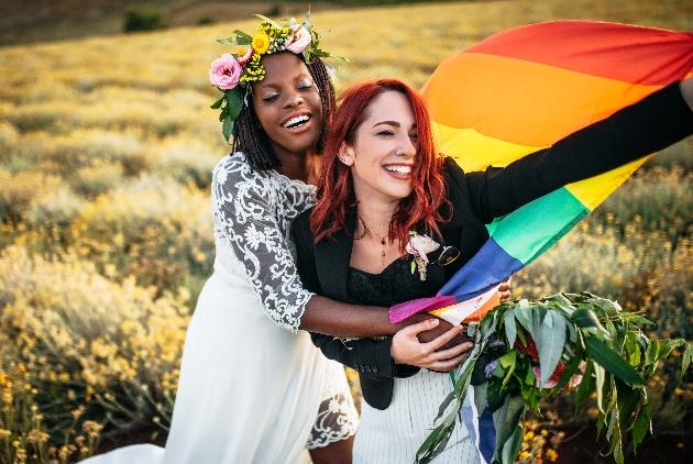 couple joyous in field in wedding outfits