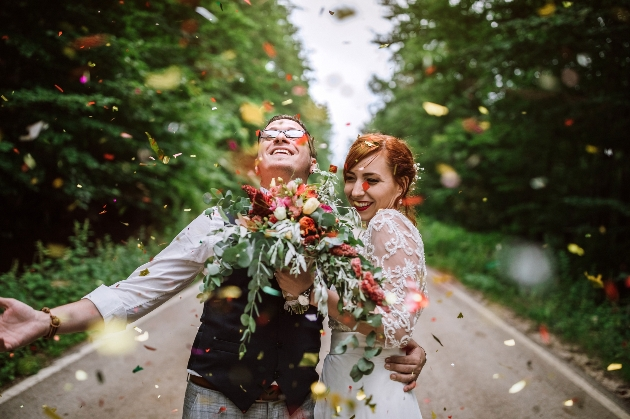couple in wedding outfits under confetti