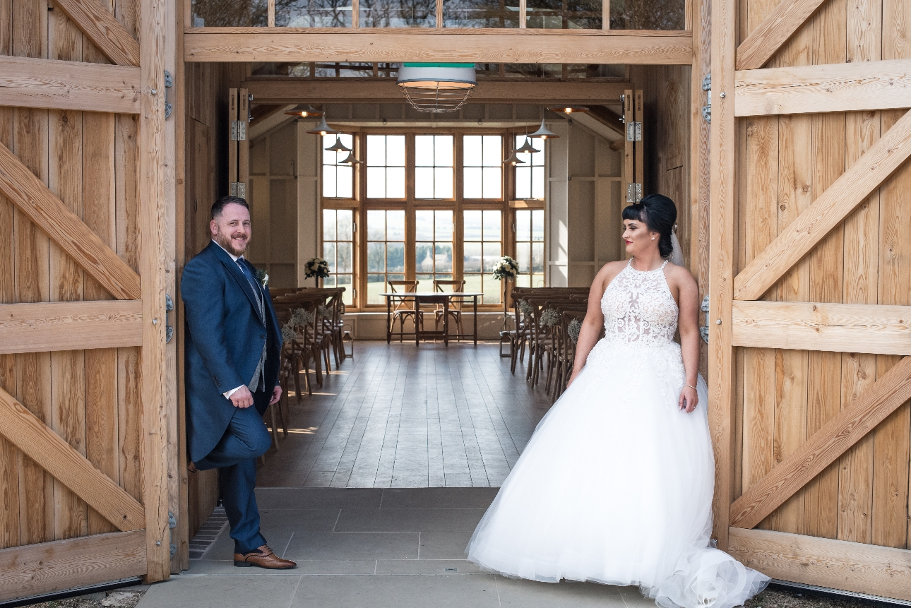 Couple pose in barn doors