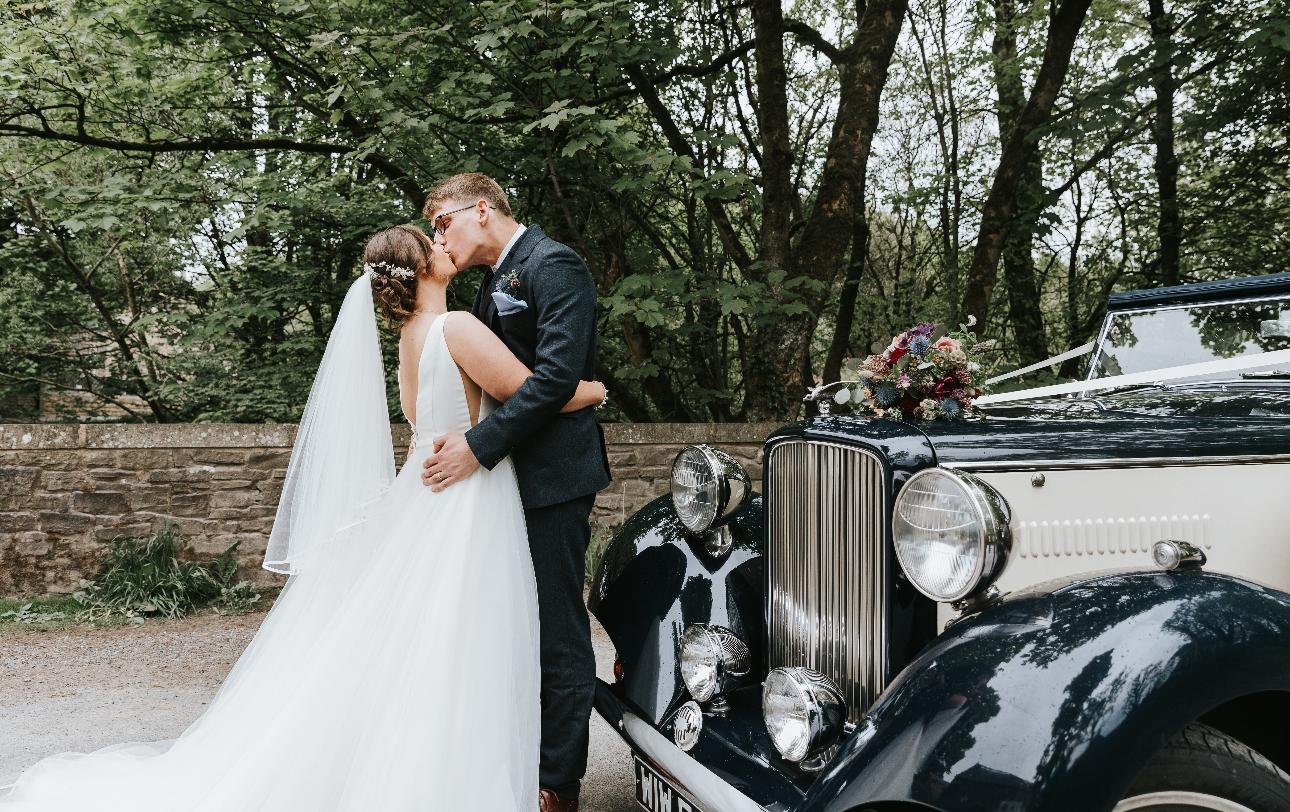 Newlyweds kiss next to car